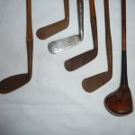 6 ANTIQUE HICKORY SHAFT GOLF CLUBS AND ANTIQUE LEATHER GOLF BAG